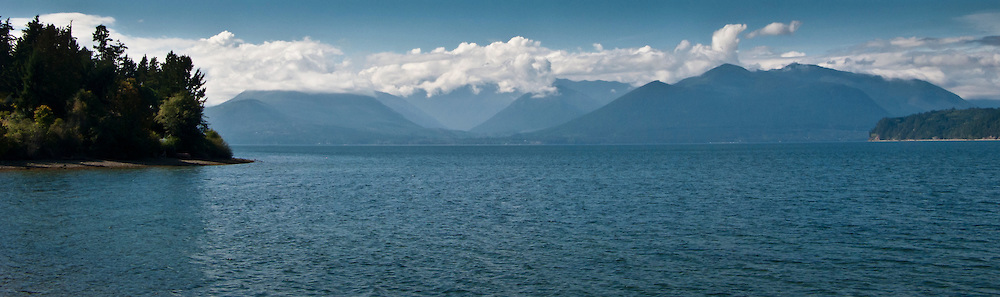 The Hood Canal and cloud capped Olympic Mountains on a sunny day panorama, part of the Puget Sound in western Washington state, USA